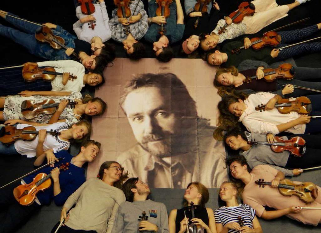 Fiolinistene ligger rundt et stort bilde av Kjell Seim