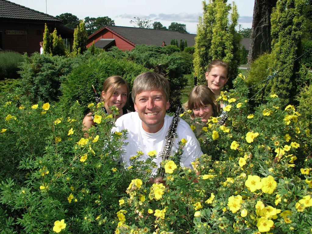 Tre glade oboister og deres instruktør blant blomstene