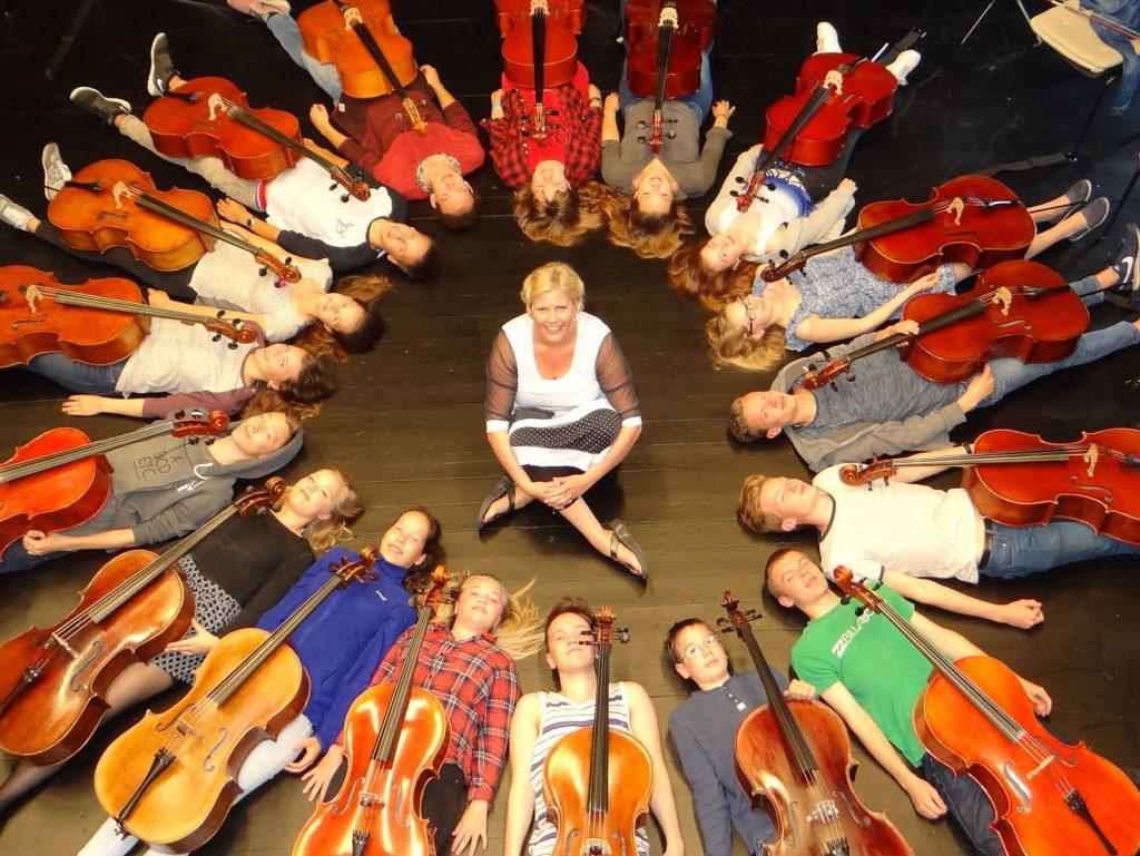 17 cellister liggende på ryggen i en sirkel med sin lærer sittende i midten