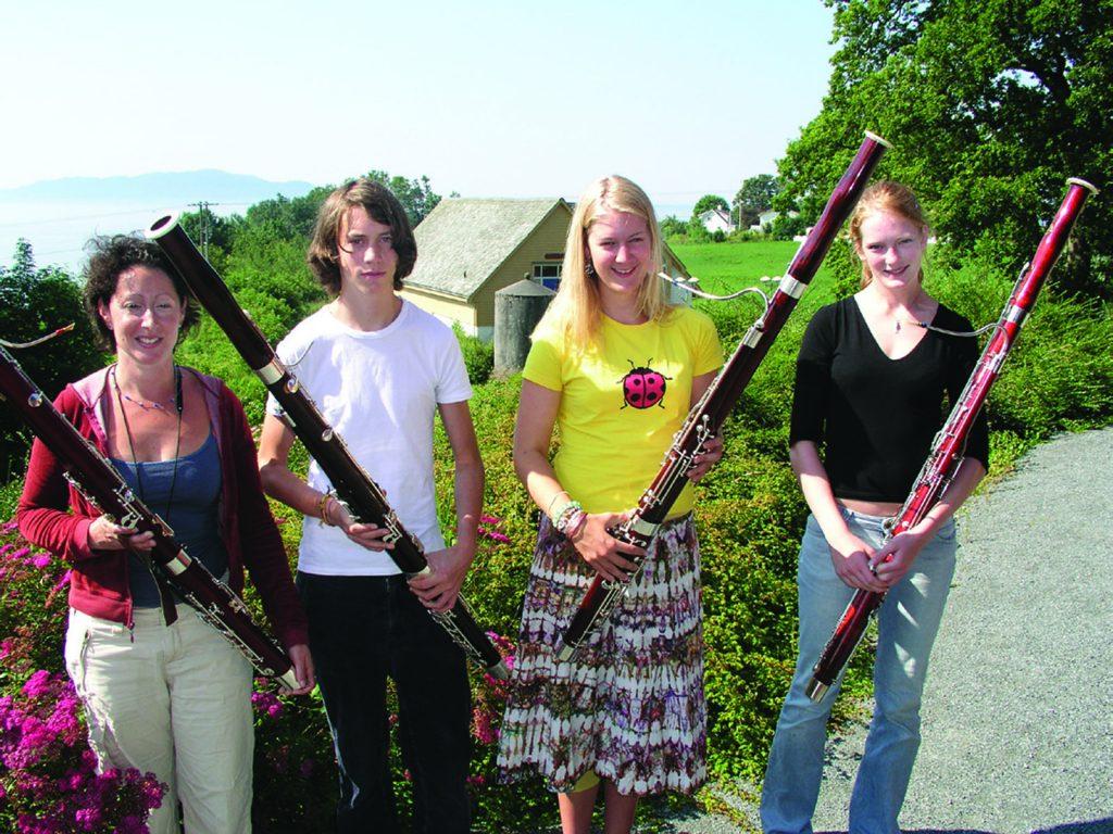 Tre unge fagottister og læreren ute i solen
