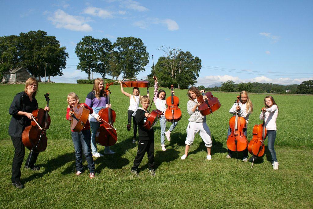 Cellister som løfter sine instrumenter på engen